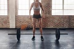 Giovane donna muscolare che si esercita con i pesi pesanti Fotografia Stock