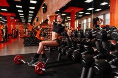 Giovane donna muscolare con il bello ente che fa gli esercizi con la testa di legno fotografie stock