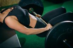 Giovane donna muscolare di forma fisica che solleva un crossfit del peso nella palestra Bilanciere del deadlift della donna di fo Fotografia Stock Libera da Diritti