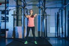 Giovane donna muscolare di forma fisica che solleva un crossfit del peso nella palestra Bilanciere del deadlift della donna di fo Fotografia Stock