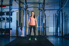 Giovane donna muscolare di forma fisica che solleva un crossfit del peso nella palestra Bilanciere del deadlift della donna di fo Immagini Stock