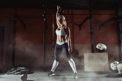 Giovane donna muscolare di forma fisica che solleva un peso nella palestra Immagini Stock Libere da Diritti