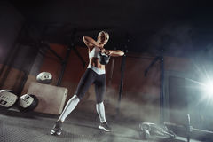 Giovane donna muscolare di forma fisica che solleva un peso nella palestra Immagine Stock