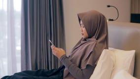 Giovane donna musulmana asiatica che per mezzo dello smartphone sul letto video d archivio