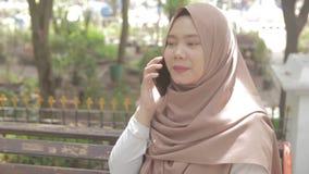 Giovane donna musulmana che si siede sul banco mentre colloqui con qualcuno sul telefono archivi video