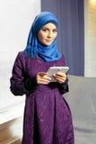 Giovane donna musulmana con una compressa elettronica in sue mani Fotografia Stock Libera da Diritti