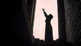 Giovane donna musulmana nel hijab che prega nella costruzione abbandonata, spaventato e preoccupato archivi video