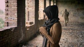 Giovane donna musulmana nel hijab che sta nella costruzione abbandonata, soldato che cammina nel fondo, militare
