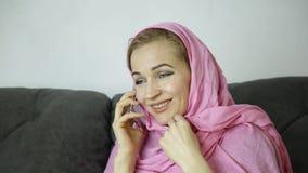 Giovane donna musulmana nel hijab rosa che si siede su un sofà in un caffè e che parla sul telefono cellulare video d archivio