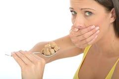 Giovane donna naturale prudente attraente che tiene una cucchiaiata di Brown Sugar Cubes Fotografia Stock Libera da Diritti