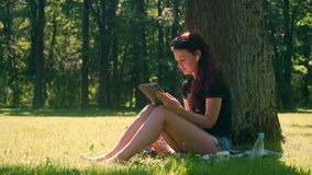 Giovane donna negli usi smartphone e compressa del parco video d archivio