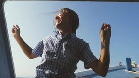 Giovane donna nei balli degli occhiali da sole su un yacht, contro il contesto del tramonto Goda di una crociera del mare, partit stock footage