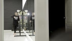 Giovane donna nel balletto dei treni degli abiti sportivi azione La giovane donna impacciata in vestiti di ogni giorno sta prende stock footage