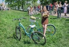 Giovane donna nel bello stile di estate con il libro di lettura del ciclo durante la retro crociera di festival all'aperto Fotografie Stock