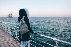 Giovane donna nel cappuccio che esamina il mare di inverno fotografia stock