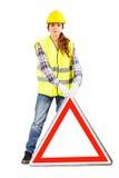 Giovane donna nel casco della costruzione con il segnale stradale Fotografia Stock
