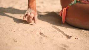 Giovane donna nel cuore del disegno del costume da bagno del bikini sulla sabbia bianca alla spiaggia tropicale dell'isola in Tai stock footage