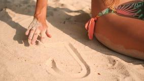 Giovane donna nel cuore del disegno del costume da bagno del bikini sulla sabbia bianca alla spiaggia tropicale dell'isola in Tai archivi video