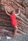 Giovane donna nel dressrock rosso-chiaro su fondo roccioso Ritratto romantico Fotografia Stock