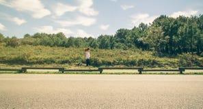 Giovane donna nel funzionamento degli abiti sportivi su una pista Immagine Stock Libera da Diritti
