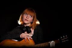Giovane donna nel gioco nero sulla chitarra Fotografie Stock Libere da Diritti
