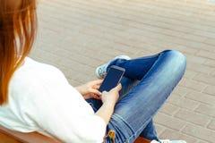Giovane donna nel parco con il telefono Fotografie Stock
