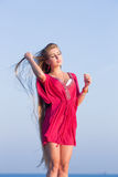 Giovane donna nel rosso che regola i suoi capelli all'aperto Fotografia Stock Libera da Diritti