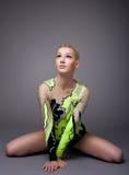 Giovane donna nel vestito del gymnast che propone sul grey Immagine Stock