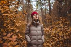 Giovane donna nell'abbigliamento casual che sta nella foresta di autunno Immagine Stock