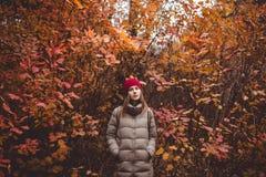 Giovane donna nell'abbigliamento casual che sta nella foresta di autunno Immagini Stock