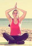 Giovane donna nell'addestramento degli abiti sportivi alla spiaggia del mare Immagini Stock
