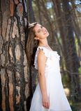 Giovane donna nell'albero facente una pausa del vestito bianco in foresta Fotografie Stock Libere da Diritti