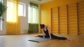 Giovane donna nell'allungamento, nella forma fisica o nell'yoga di pratica nera da solo in studio giallo minimalista Ragazza che  archivi video