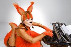 Giovane donna nell'immagine dello scoiattolo con una retro macchina da scrivere Immagini Stock Libere da Diritti