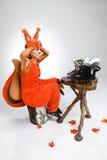 Giovane donna nell'immagine dello scoiattolo con una retro macchina da scrivere Fotografie Stock