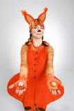 Giovane donna nell'immagine dello scoiattolo rosso con i biscotti Fotografia Stock