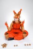 Giovane donna nell'immagine dello scoiattolo rosso con le noci Fotografia Stock