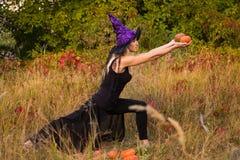 Giovane donna nell'yoga di pratica del costume della strega Immagini Stock