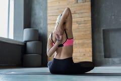 Giovane donna nella classe di yoga, allungamento della parte posteriore Fotografia Stock