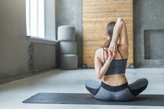 Giovane donna nella classe di yoga, allungamento della parte posteriore Immagini Stock