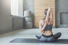 Giovane donna nella classe di yoga, allungamento della parte posteriore Fotografie Stock