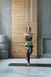 Giovane donna nella classe di yoga, asana di posa dell'aquila Fotografie Stock Libere da Diritti