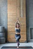 Giovane donna nella classe di yoga, asana di posa dell'aquila Immagine Stock Libera da Diritti