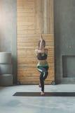 Giovane donna nella classe di yoga, asana di posa dell'aquila Fotografie Stock