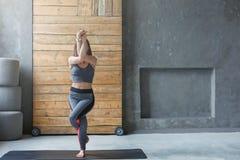 Giovane donna nella classe di yoga, asana di posa dell'aquila, spazio della copia Fotografie Stock Libere da Diritti