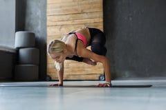 Giovane donna nella classe di yoga, asana di posa della gru Immagini Stock Libere da Diritti