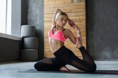 Giovane donna nella classe di yoga, asana di posa della sirena Immagini Stock
