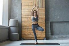 Giovane donna nella classe di yoga, asana di posa dell'albero Immagine Stock Libera da Diritti