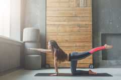 Giovane donna nella classe di yoga che fa allungando esercizio Fotografia Stock