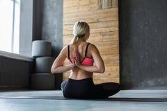 Giovane donna nella classe di yoga, posa inversa di preghiera Immagine Stock